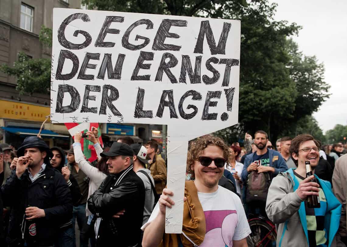 """Junger Mann mit Poster """"Gegen den Ernst der Lage!"""" während 1. Mai Demonstration, Berlin, 2014. Foto: David Vogt."""
