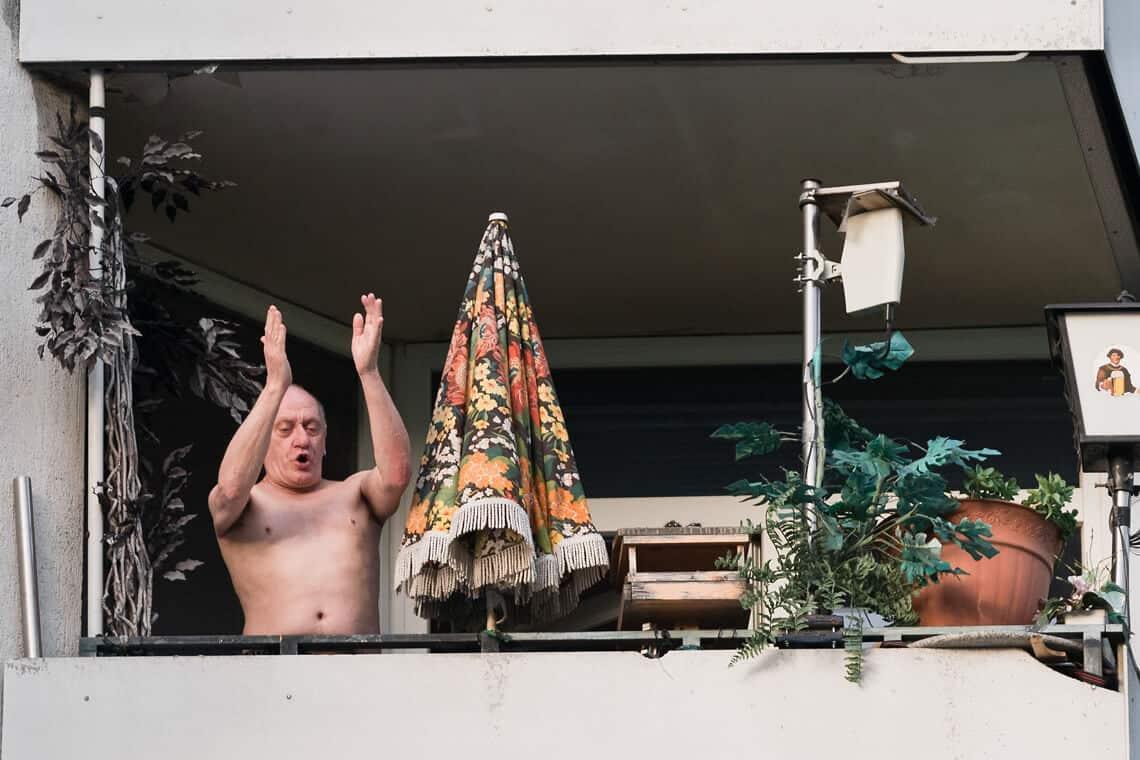 Älterer Mann mit nacktem Oberkörper jubelt 1. Mai Demonstrationszug von seinem Balkon aus zu. Berlin, 2014. Foto: David Vogt.